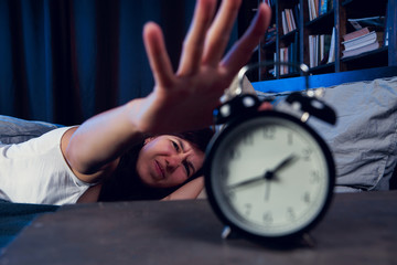 Photo of dissatisfied brunette with insomnia stretching arm to alarm clock at night