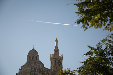 The domes of famous basilicia notre dam de la garde with the golden cross, contrails in the blue sky and branches in the blured foreground in marseilles