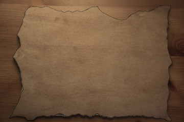 pergament like paper with burned edges on wooden desk