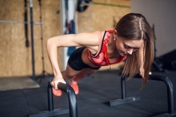 Photo of spotswoman doing horizontal push-ups with bars