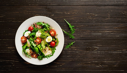 Fototapeta Fresh salad with tomatoes, mixed greens ,nuts, eggs, on wooden background . Healthy food.