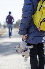 a small child holds a soft toy in his hands, and looks toward the departing mother
