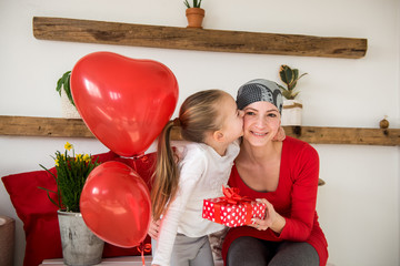 Young mother, cancer patient, and her cute daughter, celebrating return home from hospital. Welcome home or birthday party with balloons and presents.
