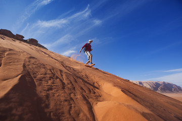 Man runs down the dune in the Wadi Rum desert, Jordan