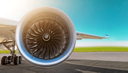 Aircraft jet engine close-up, airplane wing and chassis of landing gear wheel parked at the airport on a sky background, panorama.