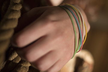 caucasion female hand with rubber bracelets band in different colors holding an old fashioned rope in s a shed