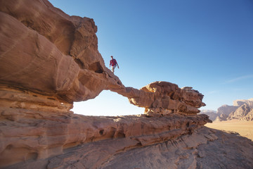 Tourist on rock. Wadi Ram desert. Stone bridge. Jordan landscape