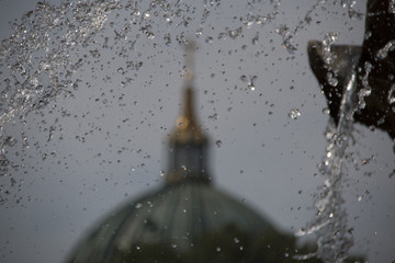 Green dome of the berlin cathedral with frozen in time water of the neptune fountain