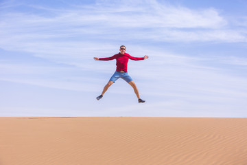 Tourist jumps on dune of Wadi Araba desert, Jordan