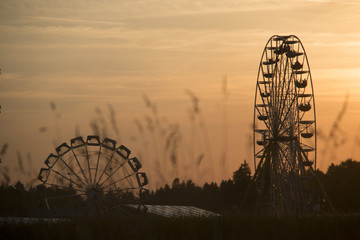 Two rotating ferris wheels in the evening sun with a cloudy orange sky and grass blades in the unfocused foreground, shot a a bavarian folk