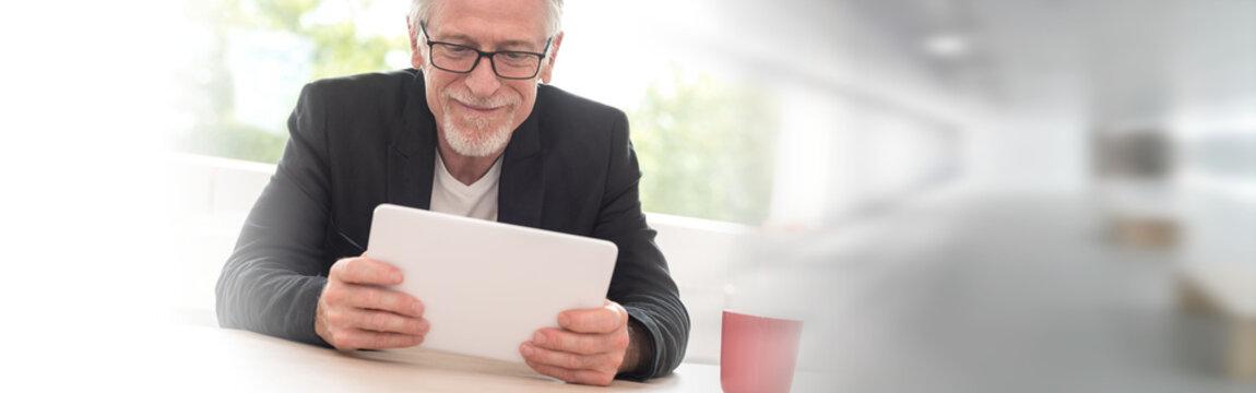 Portrait of senior businessman working on tablet