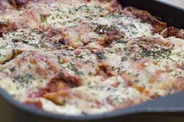 Close up shot of the topping of a italian lasagna with cheese, tomato sauce, rocket and other herbals