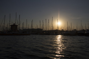 Sunset in the harbor of torrevieja with motor boats and sailing ships and the evening setting sun on the blue and orange sky