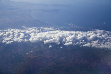 Aerial of Spanish coast in the area of alicante with a few clouds in the foreground, the blue sky on a sunny day with the horizon and the baleric sea or ocean shot form a plane