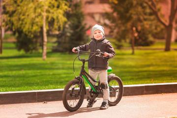 Happy little boy riding a bike