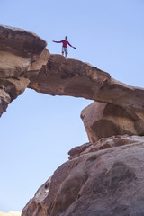 Tourist on rock. Wadi Ram desert. Stone bridge. Jordan landscape