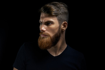 Dramatic concept Close-up portrait of young handsome bearded man looking forward. Studio shot on black background