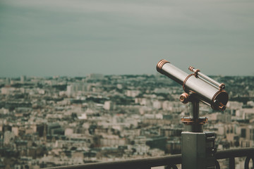 golden and silver vintage binoculars on a platform of eiffel tower with paris in background