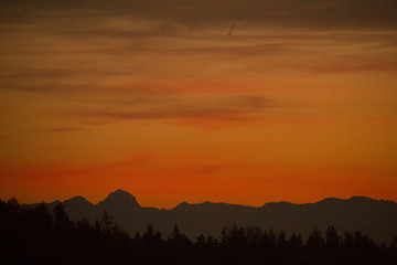 Orange silhoue tte of a dark horizon with a silhoutte of a mountain range of the alps on a sunny day evening after sunset with clouds