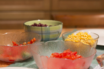 Bowls on a table with tomatoes, beans, paprika and corn