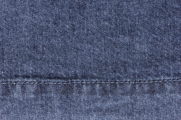 Old blue denim jeans texture or background with visible fibers and stitch
