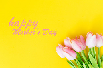 close up on group of pink petal  tulip flowers blossom lay on yellow paper texture background for mother's day design concept