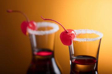 Sweet cherries on glasses of liquor.