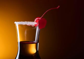 Sweet cherry on glass of liquor .