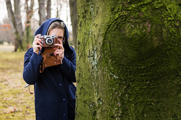 Young blonde woman in hood, hides behind a tree, holding retro photo camera and taking photo in the deep forest. Autumn nature concept. Outdoor portrait