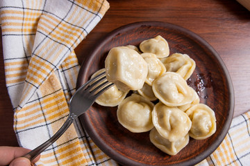 Close up view of boiled meat dumpling on metal fork. Served in clay plate Ukrainian meat dumplings or ravioli on wooden background..