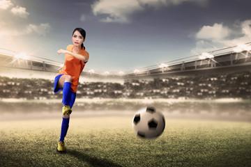 Attractive asian footballer woman kicking ball during match