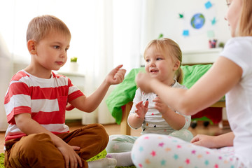 childhood, leisure and family concept - happy little kids playing rock-paper-scissors game at home