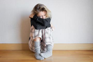 Sad woman sitting on floor