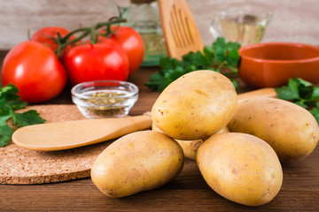Raw potatoes in the peel, vegetables, greens and spices for cooking a dish on a wooden table