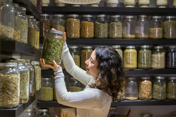 Woman taking jar with spice in shop