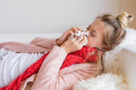 Sick woman with tissue and running nose