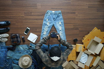 Top view of men shooting take a photo jeans pants and fashion accessories on wooden floor with postal parcel, Selling online ideas concept