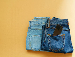 Picture of two jeans with mobile in pocket