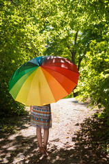 Portrait of a beautiful young woman with parasol walking through summer forest as seen from the back