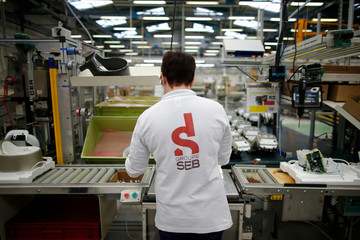 An employee works on the production line of small domestic appliances and cookware at the Groupe Seb Moulinex factory in Mayenne