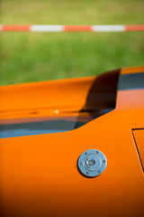 detail of a beautiful orange classic car waiting at the pit for the great race