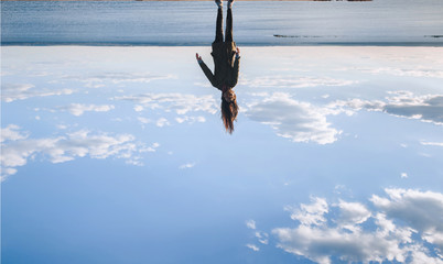 Joke concept. Cheerful girl upside down on evening sky. Lifestyle and happiness concept. Beautiful young model girl with long healthy blowing hair. Clouds, sky background.