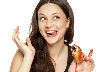 A giddy young woman eats a donut with an topping of cherry on a white background