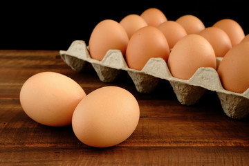 Fresh chicken eggs and egg carton on old dark brown wooden table in front of black background