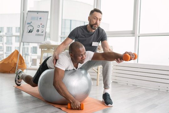 Rehabilitation exercises. Nice pleasant hard working man lying on the medball while having a workout