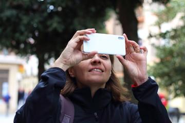 Mujer sacando una foto con el teléfono móvil  en la calle