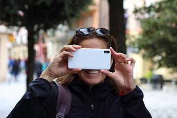 Mujer sacando una foto con el teléfono móvil de frente