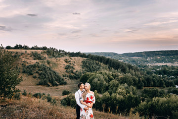 Walking A loving couple against the background of the mountains at sunset. Love story. Gentle embrace