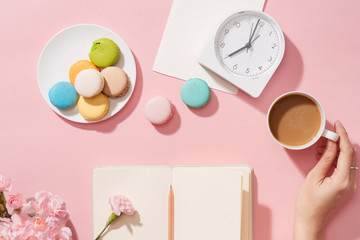 Aluminium Prints Macarons Female hand with coffee cup, macaron, office supply, gift and notebook on pastel desk top view. Fashion pink woman workplace background for blogging. Flat lay. Beautiful morning breakfast.