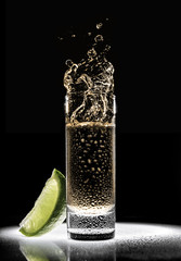 a glass of tequila with a piece of lime on a black background